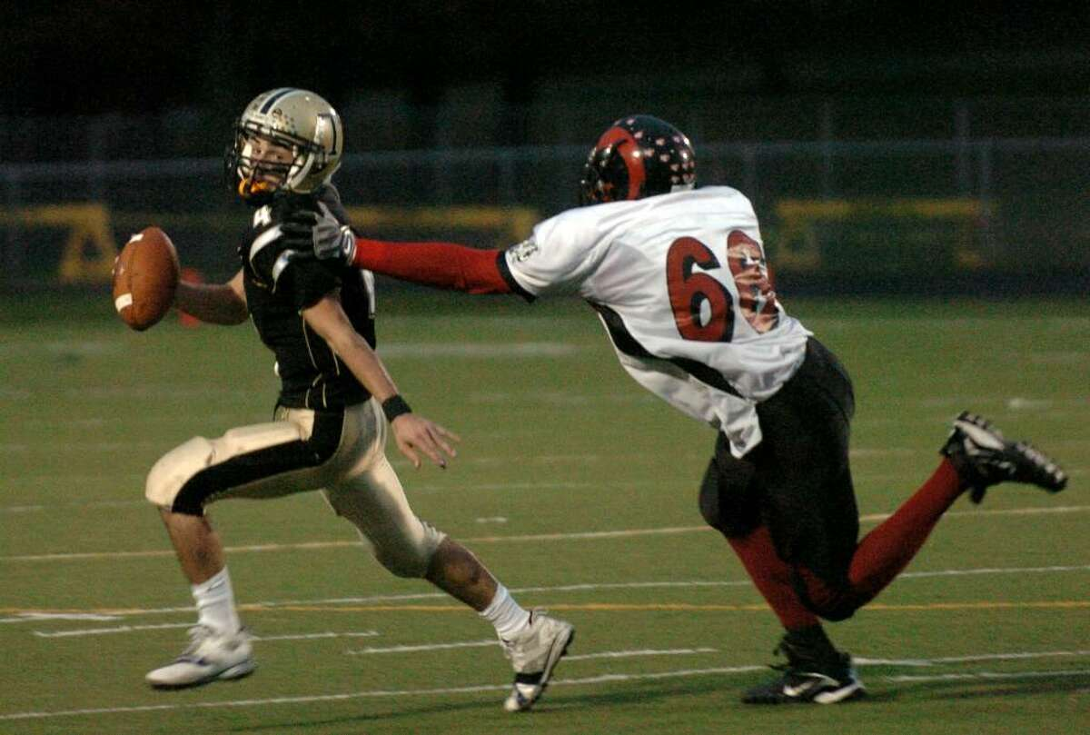 Trumbull's QB #4 Mike Romano, left, gives the slip to Central's #66 Damien Francis, during game action in Trumbull, Conn. on Friday Oct. 09, 2009.