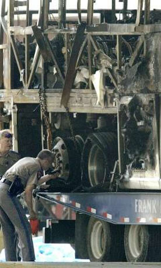 Texas troopers examine the back wheels of a bus that caught fire on Interstate 45 on Sept. 23, 2005, near Dallas. Photo: MATT SLOCUM, ASSOCIATED PRESS FILE