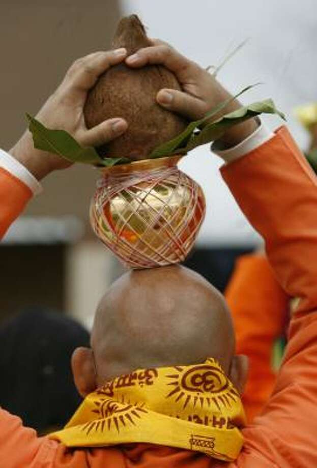 A devotee holds kalasa, a pot with water from holy rivers, atop his head for the Kumbhabhisekam ceremony of the Chinmaya Mission's temple Sri Saumyakasi in December. Photo: KEVIN FUJII, CHRONICLE