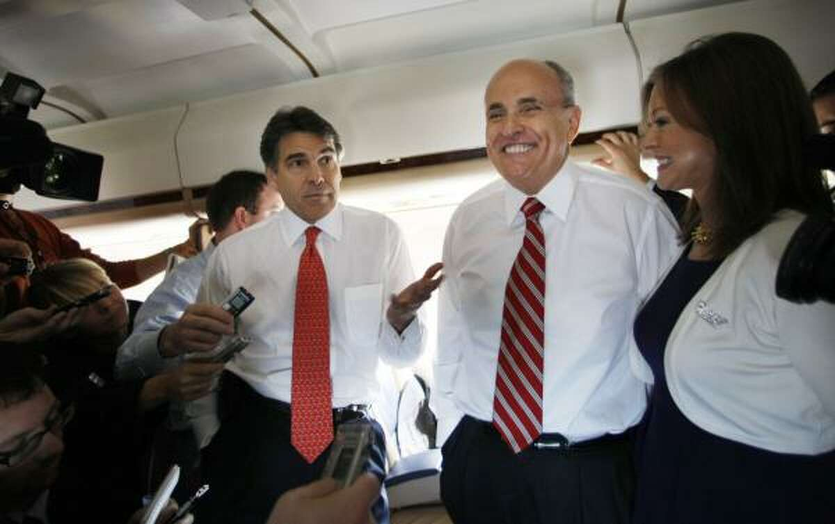 Texas Gov. Rick Perry, former N.Y. Mayor Rudy Giuliani and wife Judith Giuliani chat with reporters while campaigning Monday in Florida. Perry also helped Giuliani in Iowa and South Carolina.
