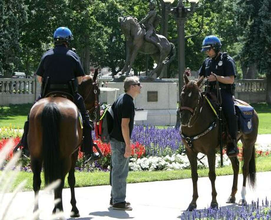 Denver Mounted Police officers talk with a man as they patrol Civic Center Park in Denver last week. As many as 200 mounted officers will be among the thousands of local, state and federal officers working the Democratic National Convention in Denver next week. Photo: ED ANDRIESKI, ASSOCIATED PRESS