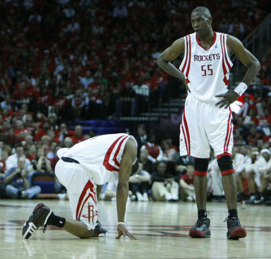 Rockets guard Tracy McGrady (left) kneels as teammate Dikembe Mutombo looks on in a playoff-opening loss to the Jazz on Saturday. Photo: Nick De La Torre, Chronicle