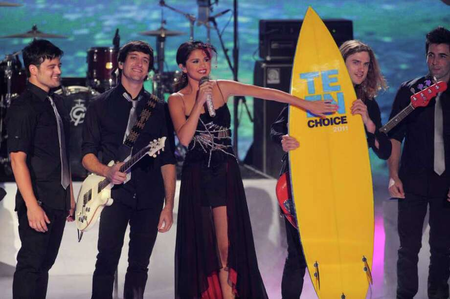 Selena Gomez, center, accepts her award onstage at the Teen Choice Awards on Sunday, Aug. 7, 2011 in Universal City, Calif.  (AP Photo/Chris Pizzello) Photo: Chris Pizzello, STF / AP