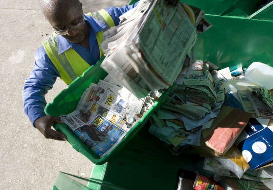 Donnie Birden with Houston's recycling program tosses newspapers into a recycling truck July 8. Photo: James Nielsen, Chronicle