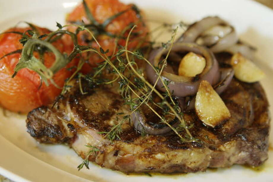 Wood-roasted ribeye steak is accompanied by a cluster of tomatoes, onions and garlic, one of the mouth-watering dishes at the Grove. Photo: Melissa Phillip, Houston Chronicle