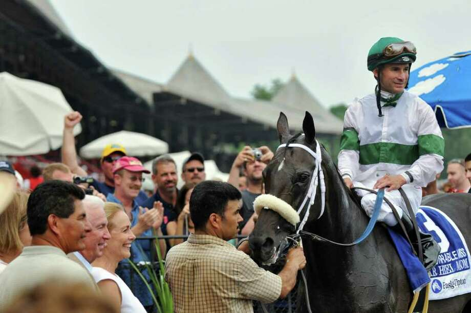 Jockey Alex Rankin and Tar Heel Mom pose for pictures in the winner's circle after winning the 20th running of The Honorable Miss race at the Saratoga Race Course on Sunday Aug. 7, 2011 in Saratoga Springs, NY.  (Philip Kamrass / Times Union) Photo: Philip Kamrass / 00014162A