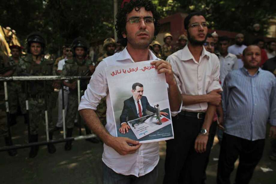 """A Syrian man holds up a poster bearing an image of Syrian President Bashar Assad during a protest against the Syrian regime, in Cairo, Egypt, Friday, Aug. 5, 2011. Syrian security forces pounded the city of Hama with tank shelling and opened fire on protesters who streamed into the streets across the country Friday calling for the downfall of President Bashar Assad, killing at least four and wounding more than a dozen. The Arabic on the sign reads """"Get out Nazi."""" (AP Photo/Tara Todras-Whitehill) Photo: Tara Todras-Whitehill / AP"""