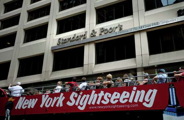 Tourists drive past Standard & Poor's headquarters in New York's financial district Saturday, Aug. 6, 2011. After the first-ever downgrade of the U.S. government's AAA credit rating by Standard & Poor's on Friday, top officials at the company on Saturday defended their position after the Obama administration called the move a hasty decision based on faulty math. (AP Photo/Karly Domb Sadof) Photo: Karly Domb Sadof