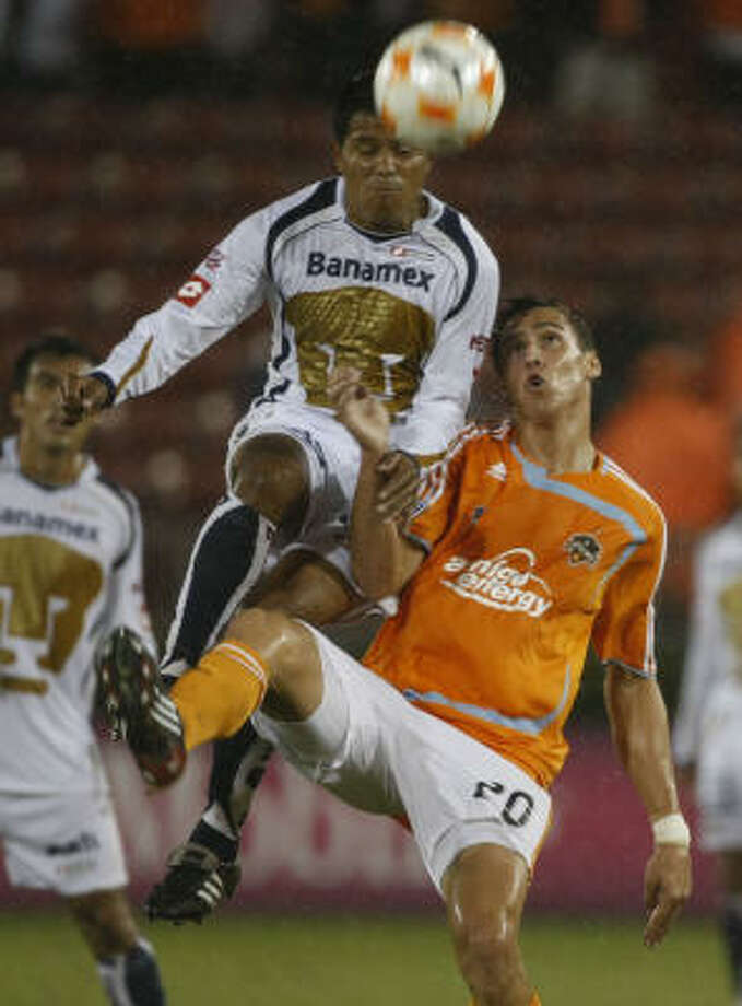 Geoff Cameron, right, of the Dynamo goes up for the ball against Fernando Santana of Mexican soccer team Pumas in the first half on Wednesday. Photo: Julio Cortez, Chronicle