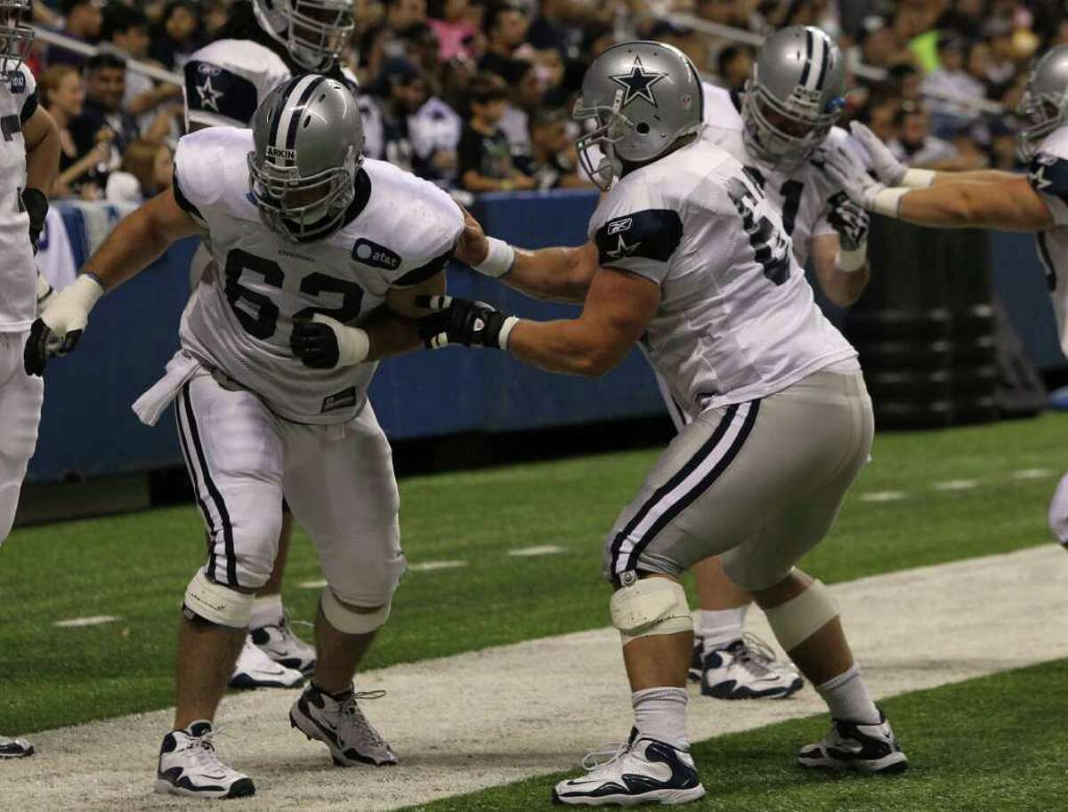 Cowboys guard David Arkin (left) goes through drills with center Phil Costa (right) before the Blue-White scrimmage on Sunday, Aug. 7, 2011. The game was part of Dallas' training camp at the Alamodome.