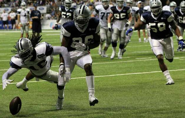 Cowboys wide receiver Jesse Holley dives for the ball in the end zone during the Blue-White scrimmage on Sunday, Aug. 7, 2011, while Josh Thomas (26) and Orie Lemon (58) give chase. The scrimmage was part of Dallas' training camp at the Alamodome. Photo: John Davenport/jdavenport@express-news.net