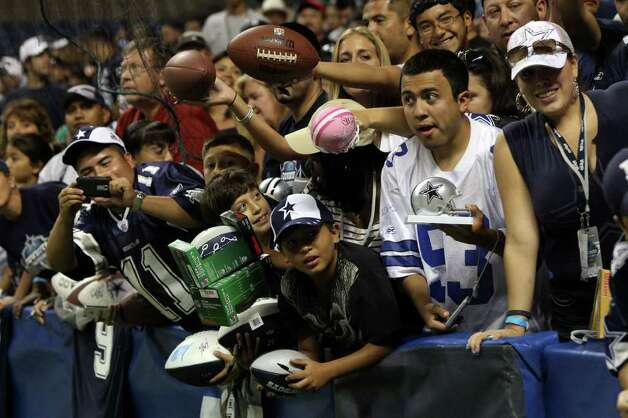 Enthusiastic Cowboys fans scream out to players hoping to get autographs after the Blue-White scrimmage on Sunday, Aug. 7, 2011. The game was part of Dallas' training camp at the Alamodome. Photo: John Davenport/jdavenport@express-news.net