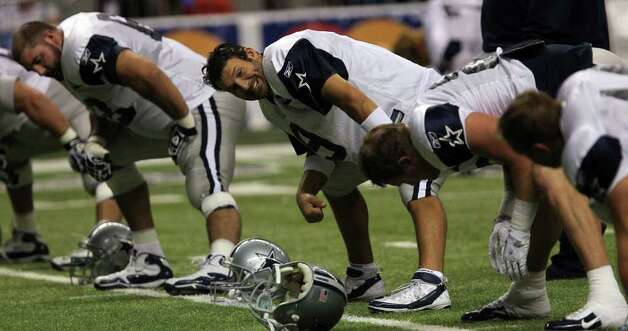 Cowboys quarterback Tony Romo (center) stretches before a Blue-White scrimmage on Sunday, Aug. 7, 2011 as part of Dallas' training camp at the Alamodome. Romo completed 16 of 20 passes for 150 yards and three touchdowns. Photo: John Davenport/jdavenport@express-news.net