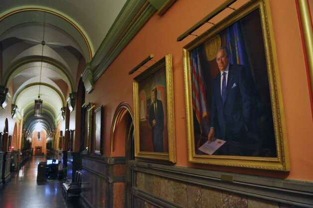 Former Gov. Hugh Carey's portrait hangs in the Hall of Governors outside of Gov. Andrew Cuomo's office in the Capitol on Sunday, Aug. 7, 2011, in Albany, N.Y.  Carey died Sunday at the age of 92. Former Gov. Nelson Rockefeller's portrait is at left. (Philip Kamrass / Times Union) Photo: Philip Kamrass
