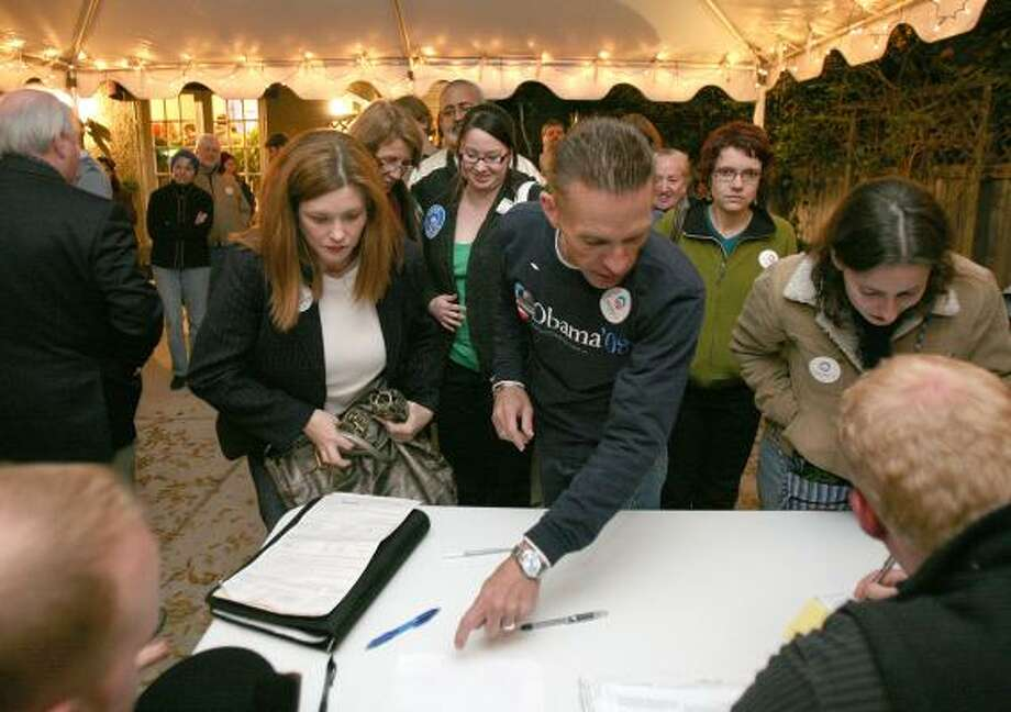 Democratic caucus chair James Bean, center, signs up delegates, including Katherine Strahan, left, and Nicole DiMucci, as a crowd jams into a hotel to support Barack Obama on Tuesday. Photo: STEVE CAMPBELL, HOUSTON CHRONICLE