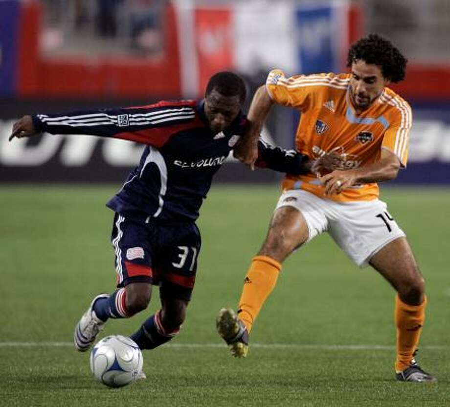 New England Revolution's Sainey Nyassi, left, and Dynamo forward Dwayne De Rosario battle for the ball during the second half of the SuperLiga final on Tuesday in Foxborough, Mass. Photo: Michael Dwyer, AP