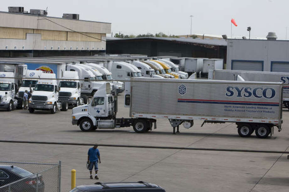 Sysco tractor-trailers prepare to move out products on Wednesday at the company's distribution center along Interstate 10 in east Houston. Photo: James Nielsen, Chronicle