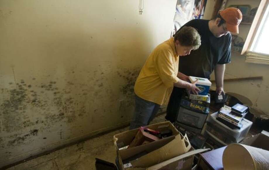 Barbara Kiker, 66, and her son Houston Kiker, 27, sort through belongings in their mold-infested Seabrook home last week. Photo: STEVE UECKERT, CHRONICLE