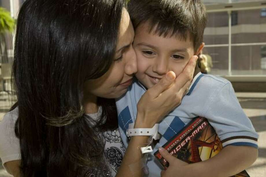 Salina Gonzales, of San Antonio, greets her 3-year-old son, Scott, on Thursday after recent surgery in Houston to have a pump removed from her heart. In 2006, her heart failing, she decided against a transplant for fear she wouldn't live long enough to see Scott grow up. Photo: BRETT COOMER, CHRONICLE