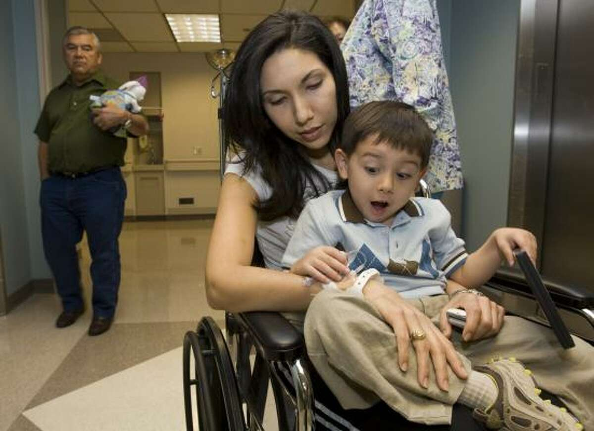 Salina Gonzales and Scott ride to her Houston hospital room Thursday. Gonzales' heart pump, along with medication, helped the teacher's failing organ recover and made a transplant unnecessary.