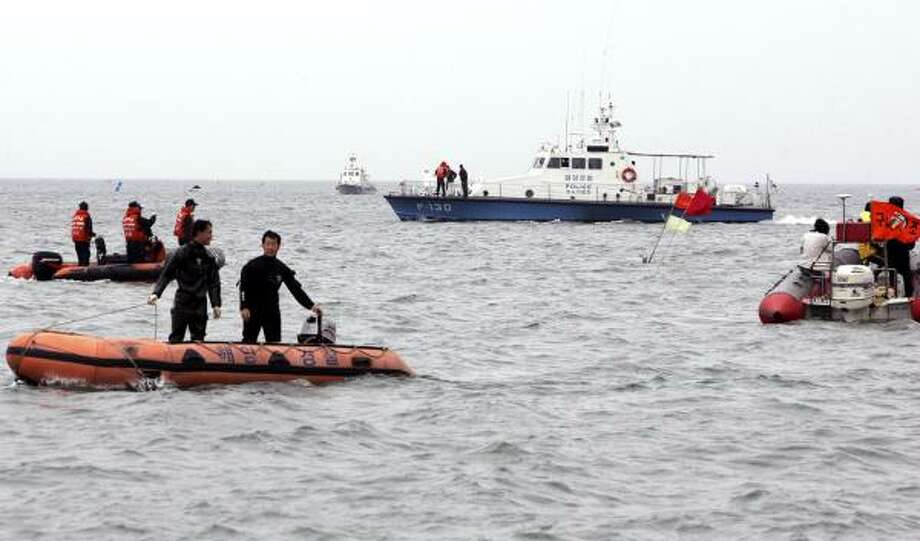 South Korean police officers search for missing persons near Daecheon Beach in Boryeong, South Korea. At least nine people were killed and 14 others injured Sunday after being swept away by a sudden large wave that crashed over a breakwater, South Korea's Coast Guard said. Photo: Kim Jun-ho, Associated Press