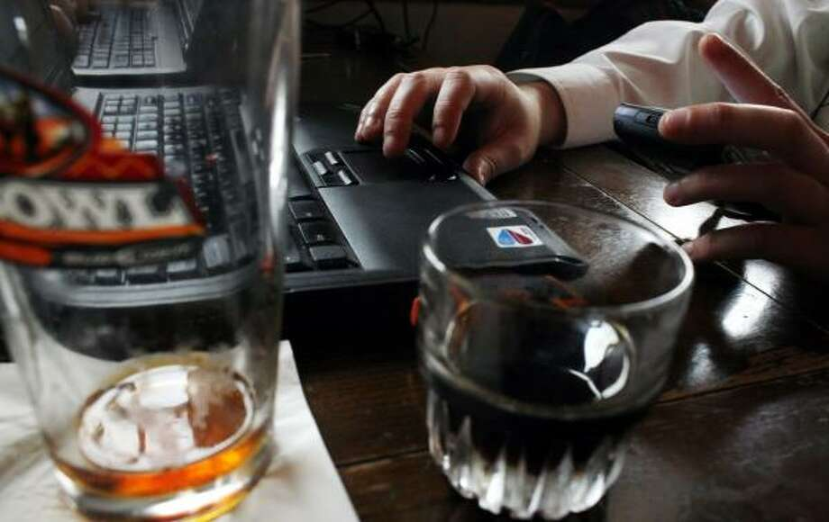 An information technology salesman who didn't want to be identified checks his phone and works on his laptop while enjoying a drink at the Stag's Head Pub. Photo: ERIC KAYNE, CHRONICLE