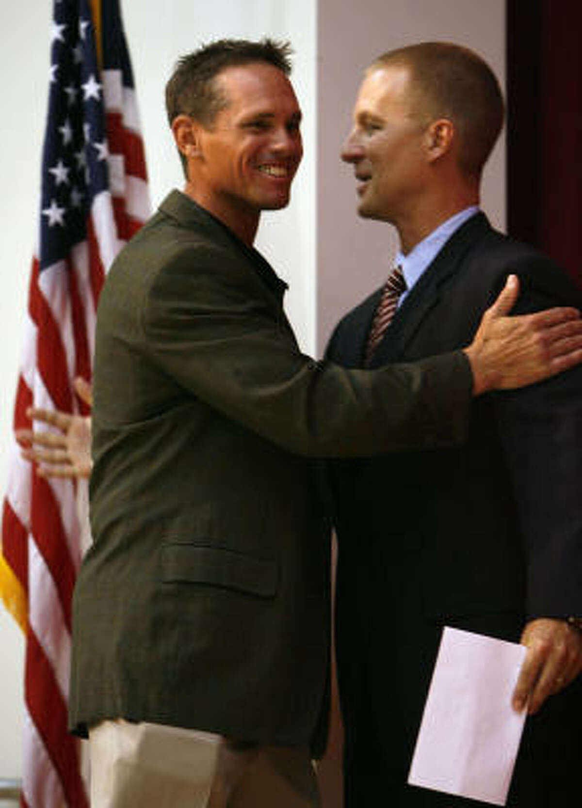 Former Houston Astro Craig Biggio (left) is greeted by St. Thomas High School's new athletic director Mike Metzel (right) during a school assembly announcing Biggio as the new baseball head coach and Donald Hollas as the new football head coach at St. Thomas High School on Tuesday in Houston.