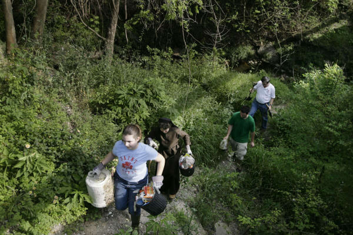 From left, Elizabeth Rinaldi, Sister Damien Marie Savino, Murray Myers and environmental studies professor William Harris walk back from planting native trees around Japhet Creek. Their buckets are filled with trash picked up along the creek bed.