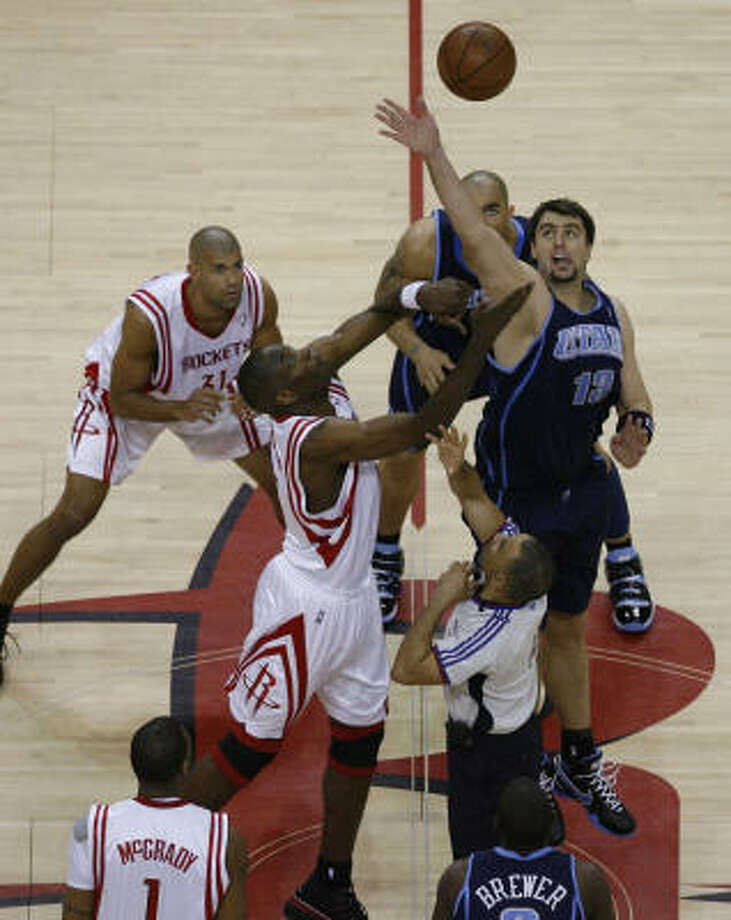 Houston's  Dikembe Mutombo, center left and Utah's Mehmet Okur, center right, jump for the ball. Photo: James Nielsen, Chronicle