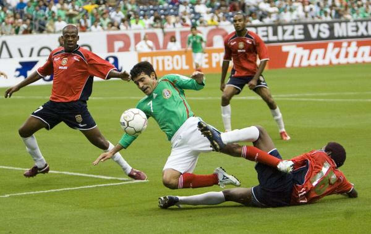 Mexico's Antonio Naelson, center, is tackled by Belize's Harrison Tasher, right, as Belize's Ian Gaynair, left, moves in to clear the ball.