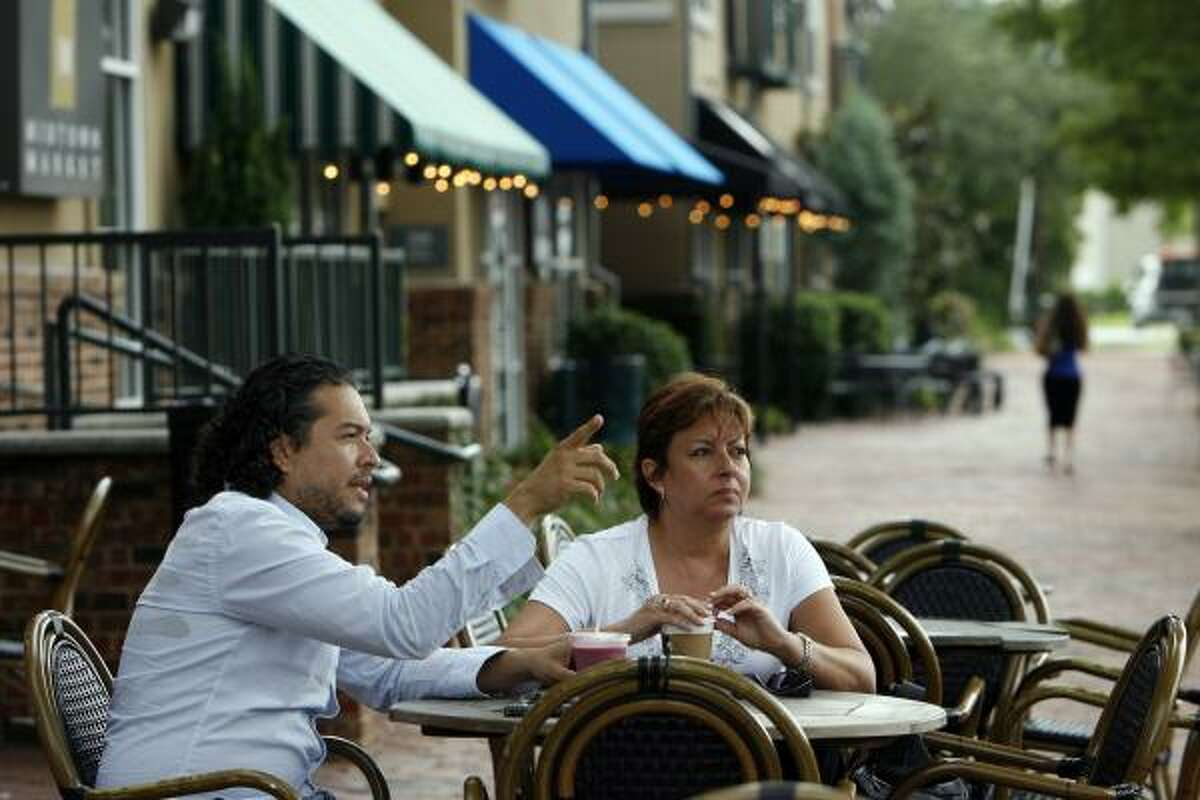 """Julio Osorio, left, and Mercedes Perez chat outside a restaurant in the 300 block of Gray. Midtown """"is a piece of Europe,"""" says Osorio. """"There are outdoor activities and restaurants, all that you can walk to."""""""