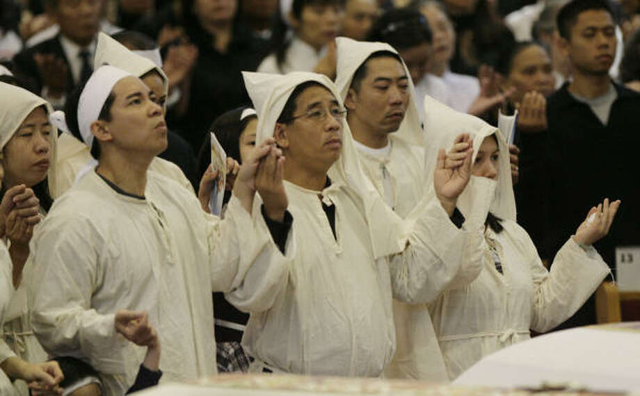 Family members of the bus crash victims in Sherman pray during funeral services at Vietnamese Martyrs Church on Saturday, Aug. 16, 2008, in Houston. Photo: Julio Cortez, Chronicle