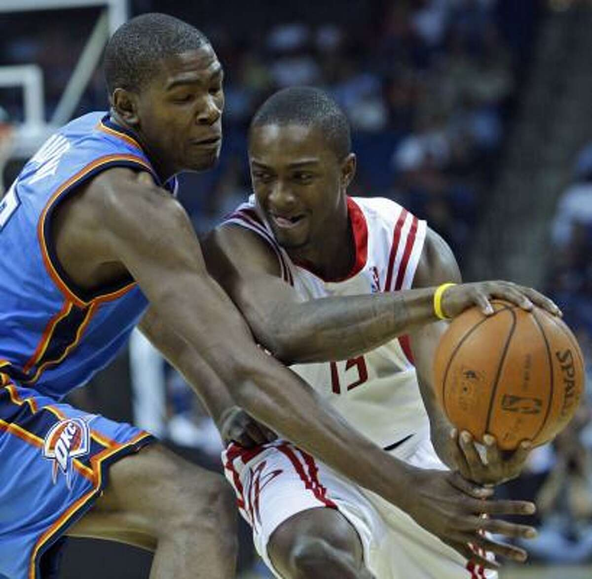 Oklahoma City Thunder guard Kevin Durant, left, reaches in to stop the drive of Rockets guard Von Wafer, right, in the first quarter on Monday in Tulsa, Okla.