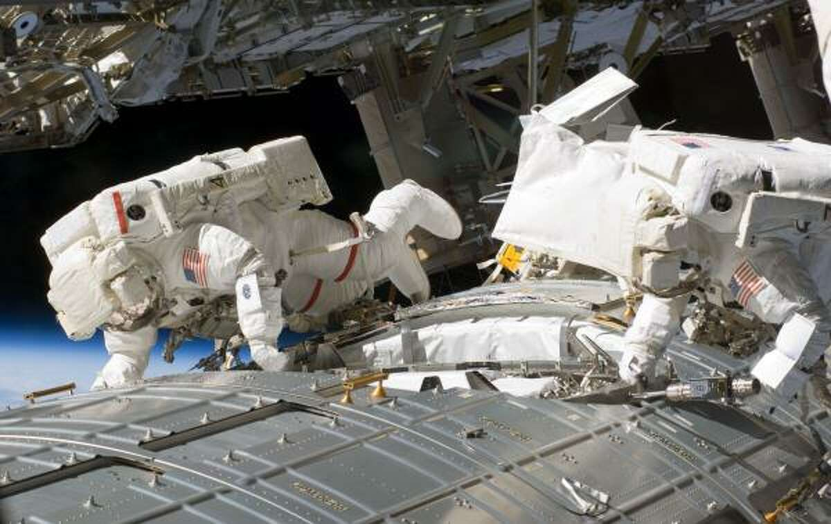 Discovery crew members Michael Fossum, left, and Ronald Garan work on the newly installed Japanese Kibo module outside the space station Thursday during the second of three planned spacewalks.