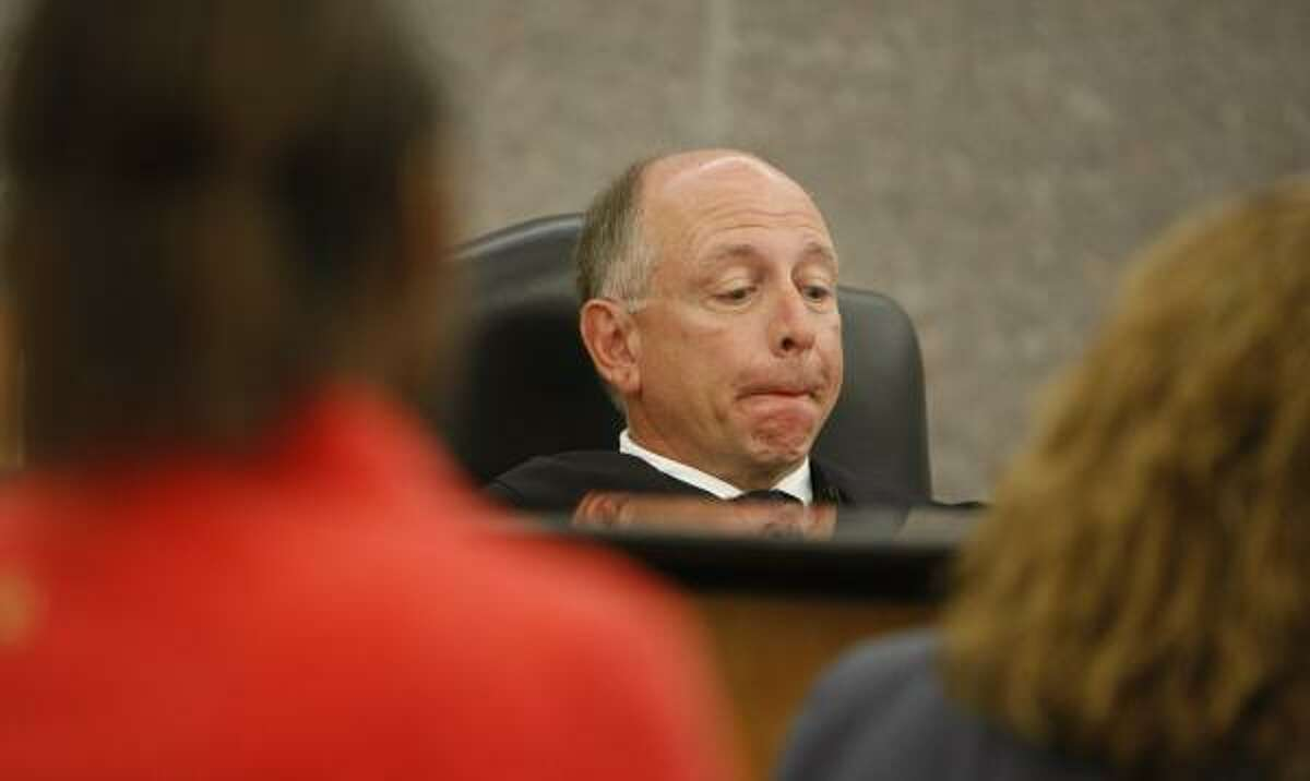 Judge John Phillips listens to caseworkers and attorneys reset a hearing date this month in Houston. He and another judge received more than 90 percent of their campaign contributions from the attorneys they appoint, according to a Chronicle analysis.