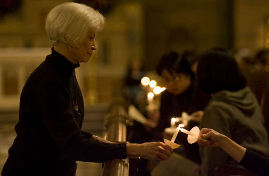 Elizabeth Turner lights candles during the Taize prayer service she helped coordinate at Villa de Matel Chapel. Photo: JAMES NIELSEN:, CHRONICLE