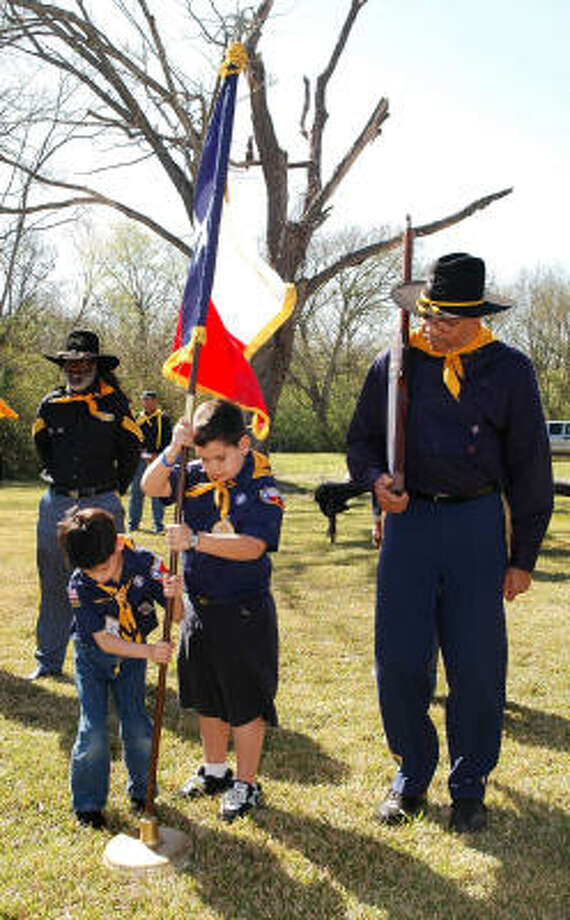 Buffalo Soldiers Trooper Cleveland Burrell, right, watches as Boy Scouts Julian Martinez, center, and Zyan Lopez of the Outley Elementary School Cub Scout Pack 1126 place the Texas flag during the historical marker ceremony at Prairie Grove Cemetery, 13685 Renn Road and Eldridge Parkway. It is one of the oldest black cemeteries in the area. Photo: George Wong, For The Chronicle