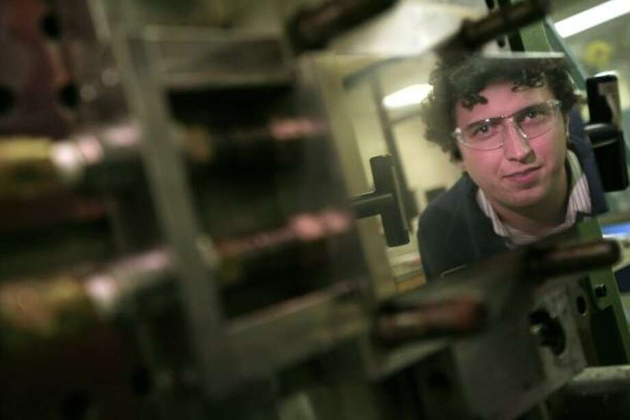 Jacob Jones, a chemical technologist at Dow, is reflected in an injection mold that produces samples of elastomer. Photo: Eric Kayne, Chronicle