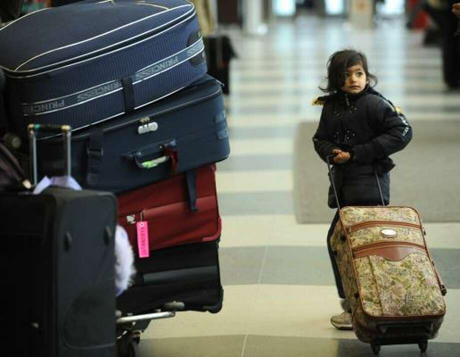 Manasvi Tyagi, 4 of Delhi, India, pulls her bag through O'Hare International Airport near the American Airlines ticket counter in Chicago on Friday. The airline canceled another 595 flights. Photo: PAUL BEATY, ASSOCIATED PRESS