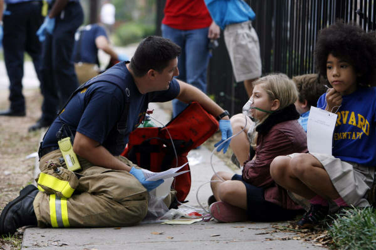 A Houston firefighter attends to a student at Harvard Elementary School after elevated levels of carbon monoxide in a classroom caused nine students and two teachers to complain of headaches and nausea.