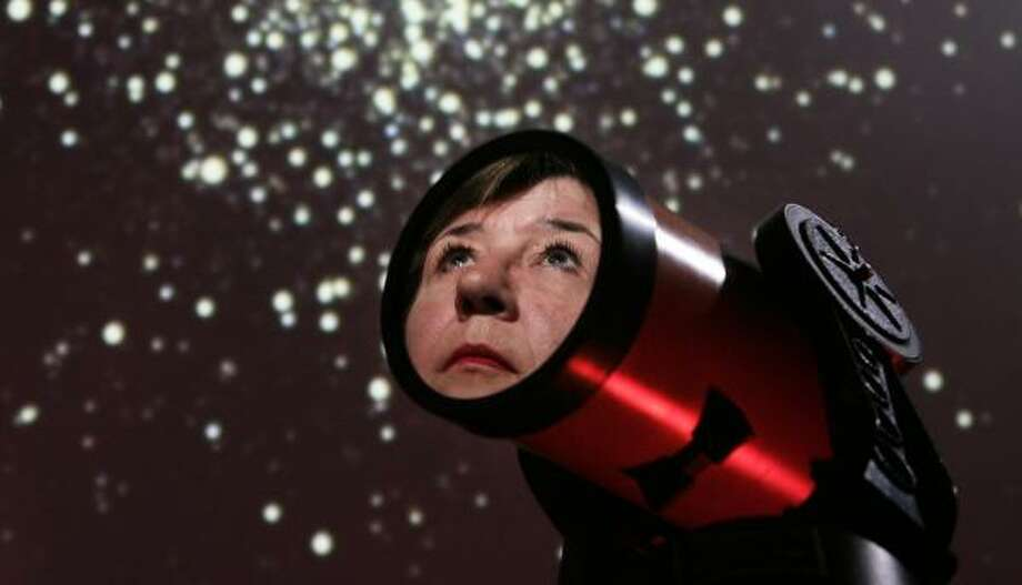 Her face reflected in a telescope, Barbara Wilson, astronomer and manager of the George Observatory, worries that light pollution is keeping a generation of children from ever seeing the wonders of a starry night. Photo: ERIC KAYNE, CHRONICLE