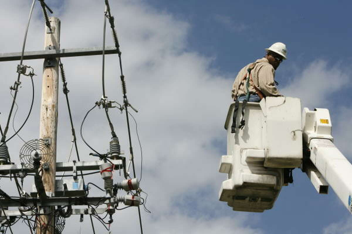 """Clarence Watkins, a head lineman for CenterPoint, demonstrates what he will normally do when working on a """"smart grid."""""""
