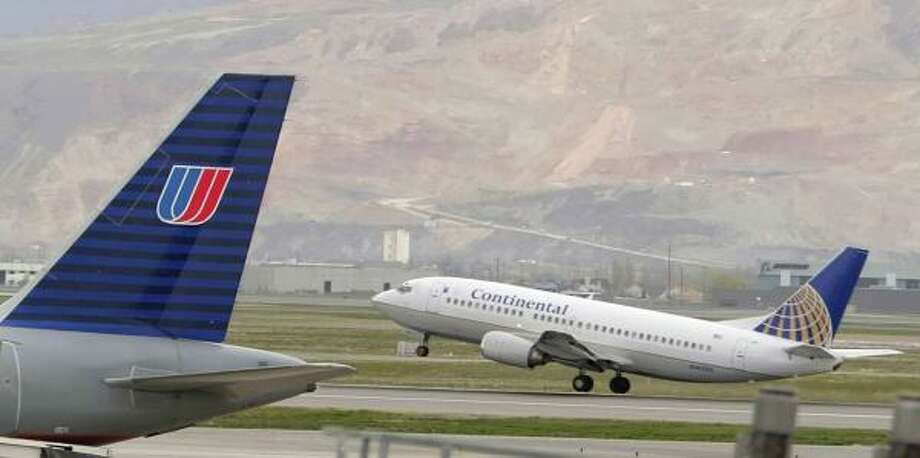 A Continental Airlines jet takes off as a United Airlines jet taxies at the Salt lake International Airport on Tuesday. Photo: George Frey, Getty Images