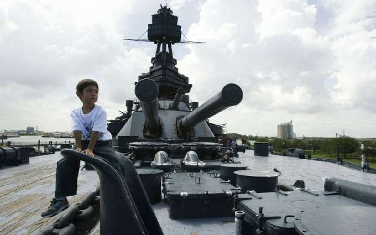 Kevin Lara, of Monterrey, Mexico, takes a break in front of the big guns while touring the battleship USS Texas at the San Jacinto Battleground on Thursday. Voters in November approved a $25 million bond issue to refurbish the aging battleship.