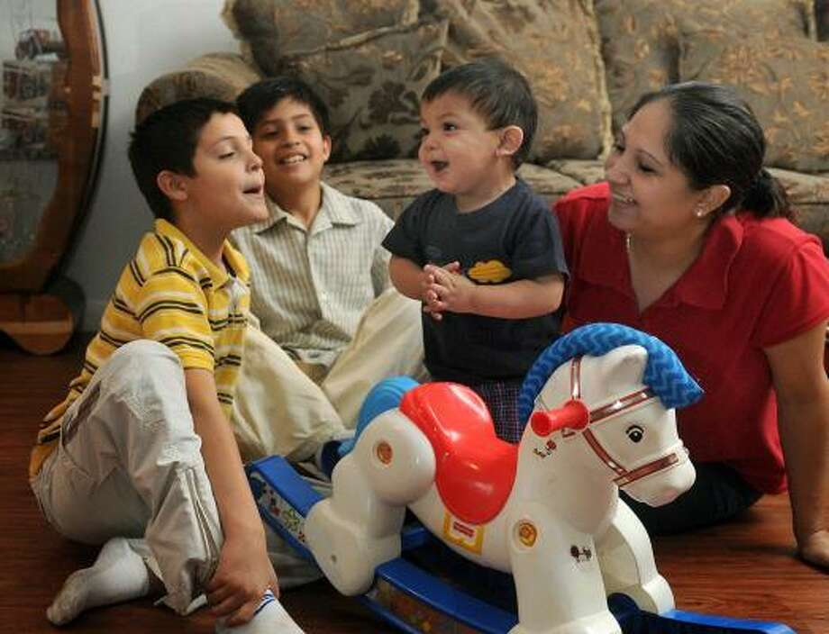Christina Reynosa enjoys a romp with sons Joel, 8, left; Isaac, 9; and Christian, 16 months, who has a rare form of epilepsy called Dravet's Syndrome. Photo: JERRY BAKER, FOR THE CHRONICLE