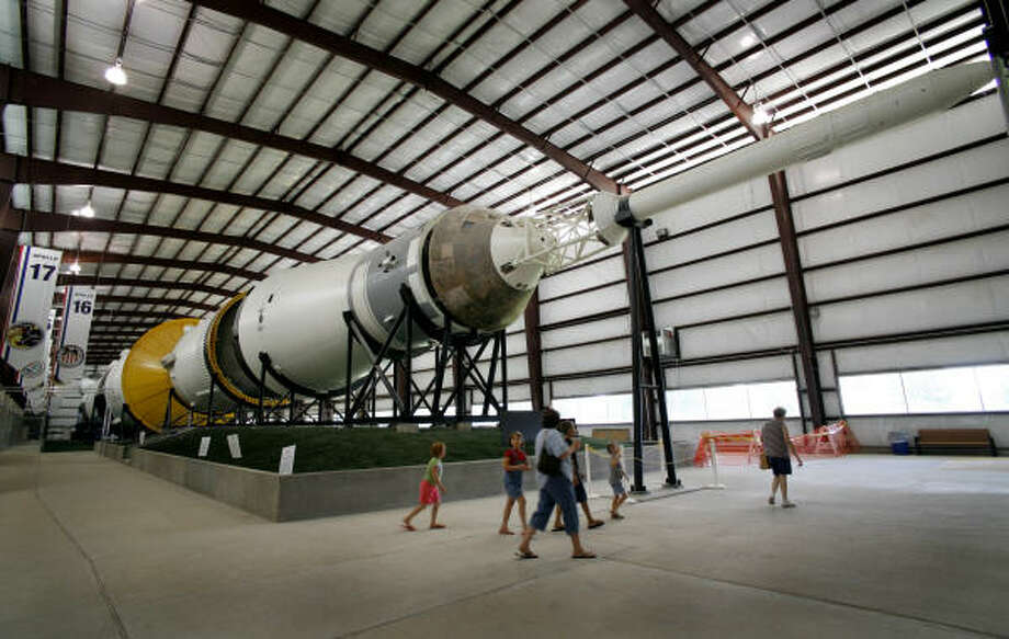 Tourists pass a Saturn V exhibit at Johnson Space Center. As the date for the shuttle's retirement nears, NASA will continually revise the projected job losses. Photo: Steve Ueckert, Chronicle File