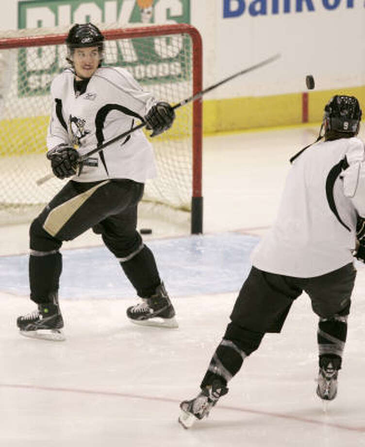 Pittsburgh Penguins' Sidney Crosby,left, swats at a puck flipped up by teammat Pascal Dupuis as the two warm up before practice in Pittsburgh, on Wednesday. The Penguins face the Detroit Red Wings in the Stanley Cup Finals first game on Saturday in Detroit. Photo: Keith Srakocic, AP