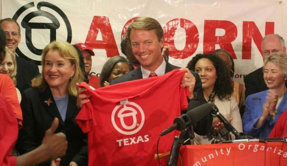 Former Sen. John Edwards holds up a Texas ACORN shirt presented to him during his visit Wednesday. Photo: GARY FOUNTAIN, FOR THE CHRONICLE