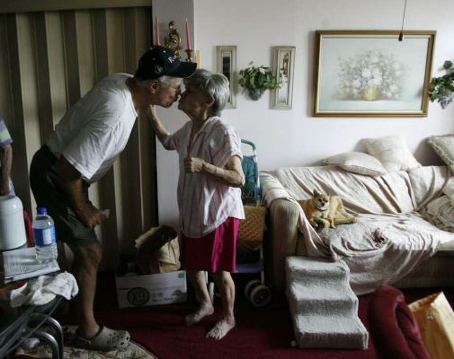 Ralph Hayes kisses Bobbie Davis, 79, after bringing food and water to her and other Heights House tenants Sunday. Photo: Karen Warren, Chronicle