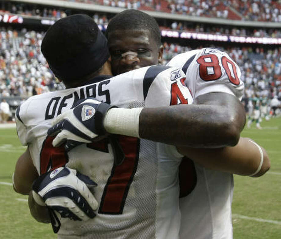 Andre Johnson, right, made amends for his third-quarter fumble with a huge catch on fourth down late in the game, earning an end-of-game hug from Will Demps. Photo: Brett Coomer, Chronicle